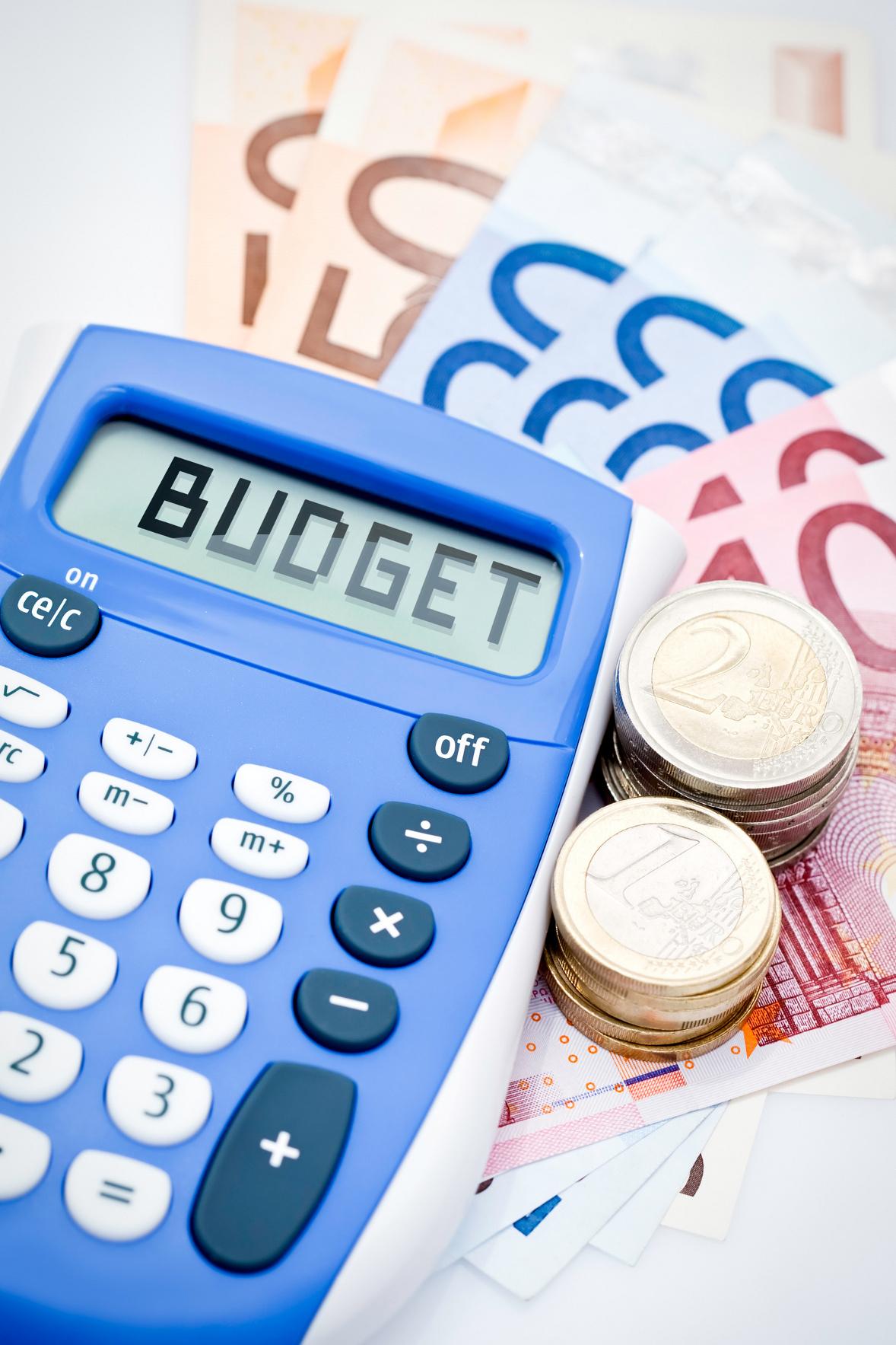 """Calculatrice indiquant le mot """"budget"""" posée sur des billets de banque"""