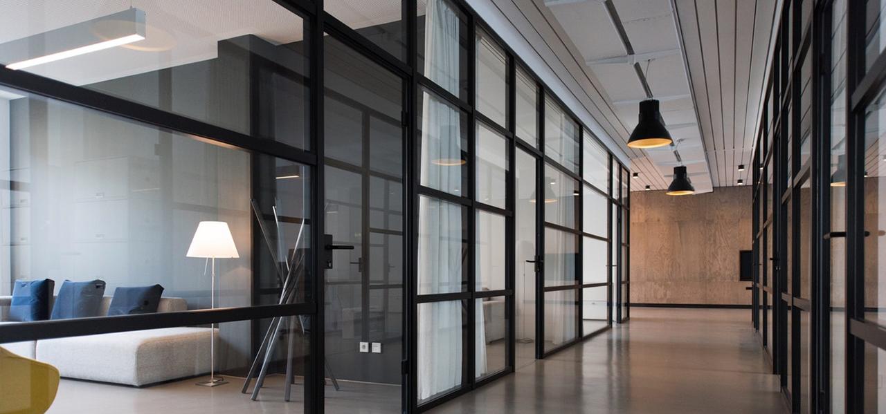 Bureaux d'entreprise aménagés avec des cloisons modulaires vitrées de style industriel